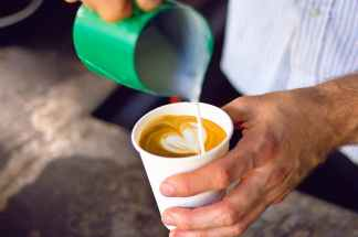 Pouring milk froth in a coffee to-go